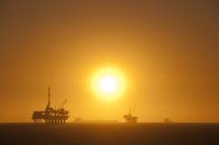Plataformas petroleras en la puesta del sol. Imagen de archivo libre de regalías