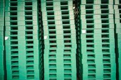 Plataformas plásticas verdes en almacén Fotos de archivo