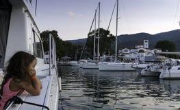 PLATAMONAS, GRÉCIA - 25 de agosto de 2018: A menina olha o mar e os barcos no porto em Platamonas, Grécia fotografia de stock royalty free