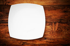 Plate. White plate on a wooden table Stock Photography