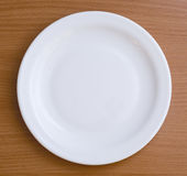 Plate. Empty plate on a brown table Stock Photography