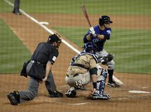 At The Plate. A hitter about to hit a pitch with catcher receiving the ball and umpire in position to make a call about balls and strikes Stock Image