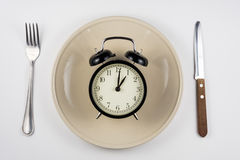 On the plate is an alarm clock, lying next to knife and fork, white background, top view Stock Image