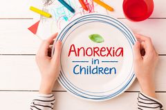 Plate with `Anorexia in Children` sign in child`s hands. Plate with a leaf and `Anorexia in Children` sign in kid`s hands. Eating disorders - concept captured stock photo