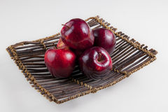 A plate of apples. Five apples on a wood plate in white background Stock Image