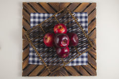 A plate of apples. Five apples on a wood plate on plaid napkin in white background Stock Photography