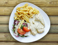 Plate with Aromatic Chicken french fries and mixed salad Royalty Free Stock Photography