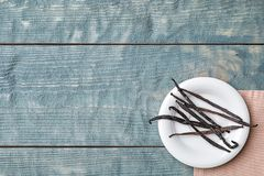 Plate with aromatic vanilla sticks. On wooden background Stock Photos