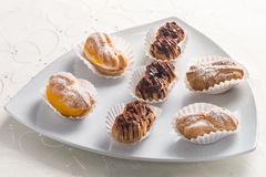 Plate of assorted eclairs Stock Images