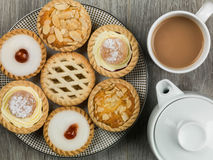Plate of Assorted Individual Cakes or Tarts With a Pot of Tea. Plate of Assorted Individual Dessert Cakes or Tarts With a Pot of Tea Stock Image