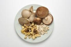 Plate with assorted mushrooms. Shiitake, king trumpet, enokitake; over white Stock Image
