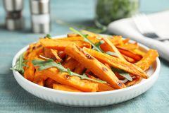 Plate with baked sweet potato slices and arugula on wooden table. Closeup royalty free stock image