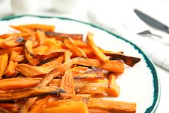 Plate with baked sweet potato slices on table. Closeup royalty free stock photos