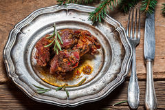 Plate with baked venison with rosemary royalty free stock images