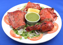 Plate of barbecue chicken. A view of a plate of barbecue chicken on a salad of lettuce and tomatoes with dipping sauce. White plate on blue background royalty free stock photography