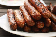 Plate of barbequed sausages on wooden table Stock Photography
