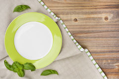 Plate with basil leaves on wooden table with tablecloth background Stock Photography