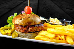 Plate with beef burger, bowl of red, white sauce, fries. stock photos