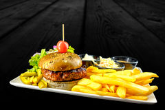 Plate with beef burger, bowl of red, white sauce, fries. royalty free stock photography