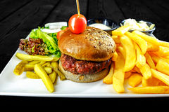 Plate with beef burger, bowl white sauce, onions. golden french fries. stock image