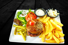 Plate with beef burger, bowl white sauce, onions. golden french fries. royalty free stock photo