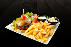 Plate with beef burger, bowl of white sauce and salad. stock images