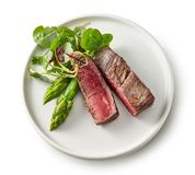 Plate of beef wagyu steak meat with herbs and asparagus. Isolated on wight background, top view royalty free stock image