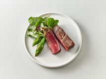 Plate of beef wagyu steak meat with herbs and asparagus. On light grey background, top view royalty free stock photo