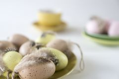 Plate with beige, pink and yellow Easter eggs, against blur pastel colored background royalty free stock image
