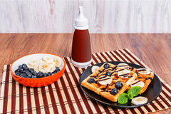 A plate with Belgian waffles and a bottle with chocolate sauce. Stock Image