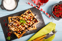 Plate of belgian waffles with chocolate sauce and currant fruit on blue wooden background. From top view. Stock Photography