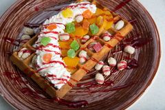 Plate of belgian waffles with  cream and candied. On ceramic brown plate Stock Images