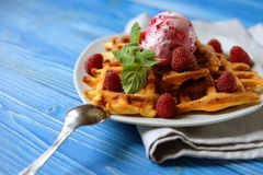 Plate of belgian waffles with ice cream and fresh berries over blue wooden background, top view. Close up Royalty Free Stock Images