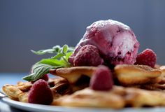 Plate of belgian waffles with ice cream and fresh berries over blue wooden background, top view. Close up Royalty Free Stock Photography