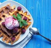 Plate of belgian waffles with ice cream  and fresh berries over. Blue wooden background, top view Stock Image
