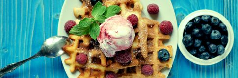 Plate of belgian waffles with ice cream and fresh berries - raspberries and blueberries.top view close-up. Plate of belgian waffles with ice cream and fresh Stock Images