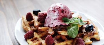 Plate of belgian waffles with ice cream and fresh berries - raspberries and blueberries. top view close-up. Plate of belgian waffles with ice cream and fresh Royalty Free Stock Photos