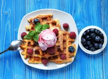 Plate of belgian waffles with ice cream and fresh berries - raspberries and blueberries.top view. Plate of belgian waffles with ice cream  and fresh berries Stock Photo