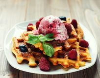Plate of belgian waffles with ice cream and fresh berries - raspberries and blueberries. top view. Plate of belgian waffles with ice cream  and fresh berries Stock Photos