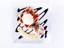 Plate of belgian waffles with ice cream and whipped cream, Strawberry sauce and bananas Royalty Free Stock Image