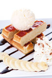 Plate of belgian waffles with ice cream and whipped cream, Strawberry sauce and bananas Royalty Free Stock Photo