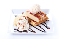 Plate of belgian waffles with ice cream and whipped cream, Strawberry sauce and bananas Royalty Free Stock Photos