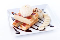 Plate of belgian waffles with ice cream and whipped cream, Strawberry sauce and bananas Stock Photos