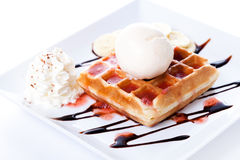 Plate of belgian waffles with ice cream and whipped cream, Strawberry sauce and bananas Stock Images