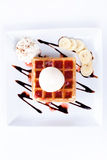 Plate of belgian waffles with ice cream and whipped cream, Strawberry sauce and bananas Stock Image