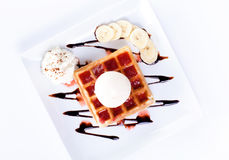 Plate of belgian waffles with ice cream and whipped cream, Strawberry sauce and bananas Stock Photography