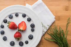 Plate with berries and bouquet of grass on white Royalty Free Stock Photo
