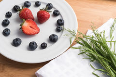 Plate with berries, bouquet of grass on white Royalty Free Stock Photography