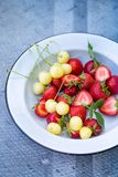 Plate with berries on a gray. Ripe strawberries and yellow cherries in a plate Royalty Free Stock Photos