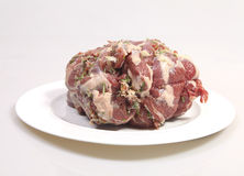 Plate with big piece of stuffed lamb. Close up of a stuffed leg of lamb with rosemary, garlic and raw ham Stock Photos